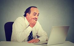 Desperate middle aged employee man working on computer in his office - stock photo