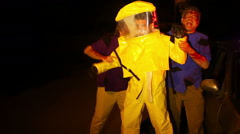 Zombies killing victim in hazmat suit Stock Footage