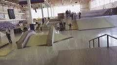 Roller skater in hat accelerate ride on springboard, get a spill in skatepark Stock Footage
