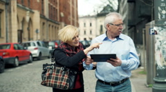 Mature couple lost in city and checking map on tablet computer Stock Footage