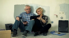 Mature couple with smartphone and tablet talking on floor at their new home Arkistovideo