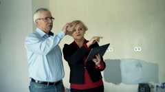 Mature couple with tablet computer talking about their new home project Stock Footage