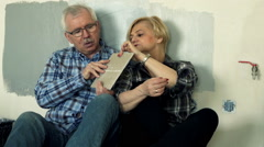 Mature couple talking and checking tile sitting on floor at their new home  Stock Footage