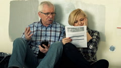 Overwhelmed mature couple counting bills with smartphone sitting on floor Stock Footage