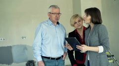 Real estate agent with tablet showing mature couple new home Stock Footage