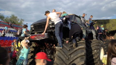 Children climb a huge monster truck. Arkistovideo
