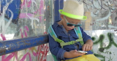 Boy with smartphone at grungy city bus stop - stock footage