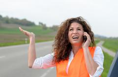 Exasperated young female driver on her mobile - stock photo
