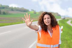 Frantic young woman trying to stop traffic Stock Photos