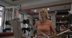 Mature woman exercising on fitness machine Stock Footage