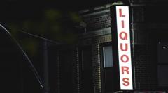 Illuminated Liquor store sign establishing shot Stock Footage