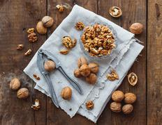 Glass bowl with walnuts on rustic homespun napkin. Healthy snack on old woode Stock Photos