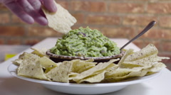 Hand dips tortilla chip in guacamole. - stock footage