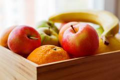 Wooden box full of fresh fruits. Fruit harvest - apples, oranges, banana, lem - stock photo