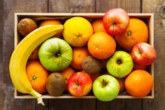 Box full of fresh fruits. Fruit harvest - apples, oranges, lemon, kiwi, banan - stock photo
