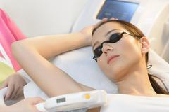 Beautiful woman getting laser hair removal at beauty salon Stock Photos