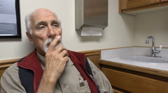 Aging man waiting impatiently in exam room to see doctor Stock Footage