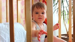 baby sitting and smiling in cot - stock footage
