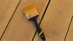 Brush with yellow paint on wooden floor Stock Footage