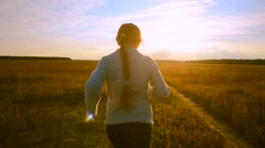 Girl runs at sunset along the road and looking back laughing Stock Footage