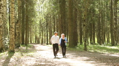 Man and woman talking and smiling,making a morning walk in the Park. Stock Footage