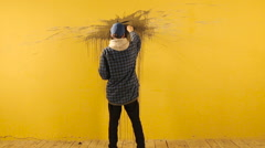 Artist paints the abstract ornament with black brush on yellow wall Stock Footage