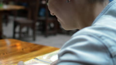 a Girl With Short Hair in a Cafe Reading the Menu - stock footage