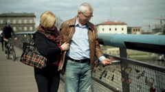 Mature couple walking on bridge and looking at their love symbol  Stock Footage