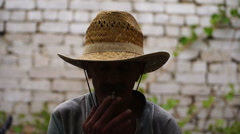 Man in a hat took refuge from the sun in the shade, smoking a cigarette Stock Footage
