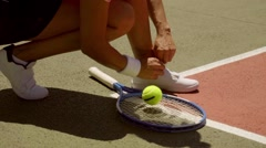 Female tennis player tying her laces Stock Footage