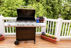 Open barbecue cooker and bottled beer on cedar wood outdoor deck - stock photo