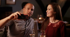 4K Attractive mixed ethnicity couple drinking wine in a bar pose for a selfie - stock footage