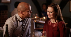 4K Affectionate couple enjoying drinks in bar lean in to kiss & smile to camera - stock footage
