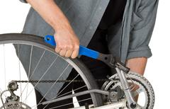 Man fixing pedals on a bicycle - stock photo