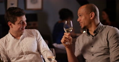 4K Attractive smart-casual men chatting, laughing & drinking wine in a bar - stock footage