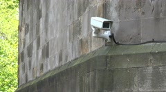 Security camera fixed to stone wall with trees in background Stock Footage