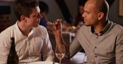 4K 2 Men enjoying dinner in a restaurant, man offers friend a taste of his meal Stock Footage