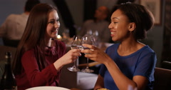 4K Close female friends eating dinner in a restaurant raise their wine glasses f Stock Footage
