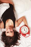 Sexy lazy girl lying with clock on bed in bedroom Stock Photos