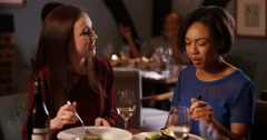 4K Close female friends catching up on the gossip over dinner in restaurant Stock Footage