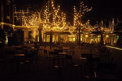 Empty night restaurant, lot of tables and chairs with noone, magic fairy lights Kuvituskuvat