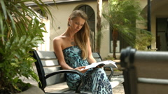 4k, Young, beautiful woman sitting on bench and reading book in city Stock Footage