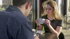 On a date, a cute couple tell a story over coffee Stock Footage
