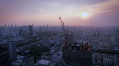 aerial top view at crane construction working and bangkok city area at twilight - stock footage