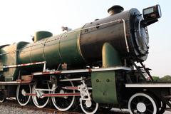 A detail closeup of a steam locomotive releasing steam. Vintage train popular - stock photo