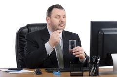 Very busy man takes pill in front of monitor - stock photo