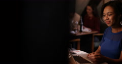 4K Thoughtful woman sitting alone in a bar & working on laptop at night Stock Footage