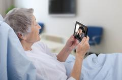 Aged woman in hospital ward using digital tablet - stock photo