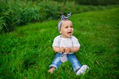 A little baby in a denim clothes sits on a grass - stock photo
