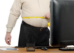 Businessman measures his big waistline - stock photo